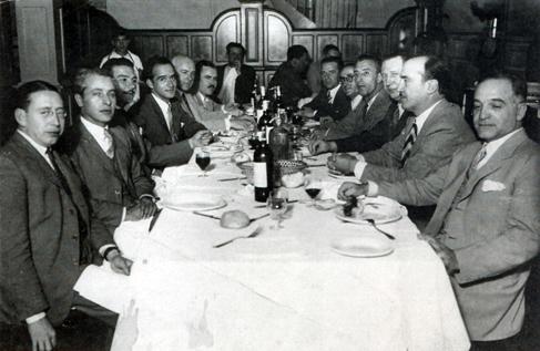 Antonio Pedone y Deodoro Roca (en segundo lugar a cada lado de la mesa) comparten una reunión con artistas, ca. 1935